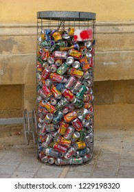 Nicosia, Cyprus - July 26, 2004: metal basket for disposal of beverage cans, it is nearly full, brands like coca cola, fanta, sprite, 7up can be seen inside