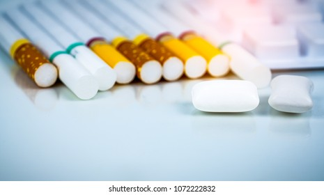 Nicotine chewing gum in blister pack near pile of cigarette. Quit smoking by use nicotine gum for relief of nicotine withdrawal symptoms. Medicine for giving up smoking. World no tobacco day concept.