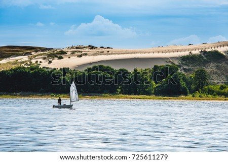 NIDA, CURONIAN SPIT, LITHUANIA - September 7, 2017. Parnidis dunes and small yacht in a curonian lagoon.