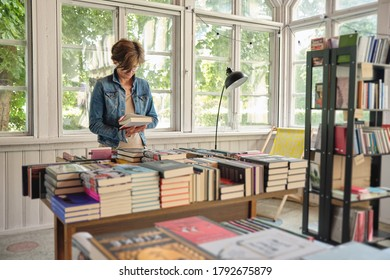 NIDA, LITHUANIA - 25 JULY, 2020: Lonely middle aged caucasian woman reading a book in vintage bookshop
