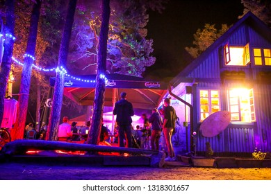 Nida, Lithuania - August 15, 2018: Young people are siting in a beautiful purple light decorated outdoor bar Zuikio darzas in Nida Lithuania. It is known as a hipter and counter culture center.