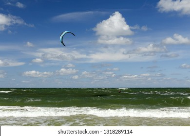 Nida, Lithuania - August 5, 2018: Kite surfer (Kiter) on green waves in Baltic sea. In Nida - a popular Lithuanian beach resort located in Curonian Spit.