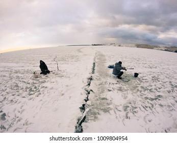 Nida, Lithuania - january 28 2016: Fishermen fishing on broken ice, Baltic Sea