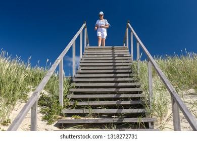 Nida, Lithuania - July 6, 2018: Young girl is walking on wooden beach stairs from dunes to the sea. On a sunny day with blue cloudless sky in Nida, on of the most beautiful Lithuanian beach resorts.