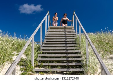 Nida, Lithuania - July 6, 2018: Two women are walking on wooden beach stairs from dunes to the sea. On a sunny day with blue cloudless sky in Nida, on of the most beautiful Lithuanian beach resorts.