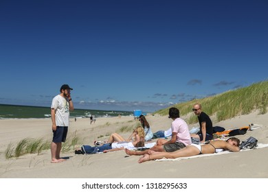 Nida, Lithuania - July 6, 2018: Group of young people are sunbathing on a Baltic sea beach in Nida - a popular summer resort in Lithuania, located on Curonian Spit.