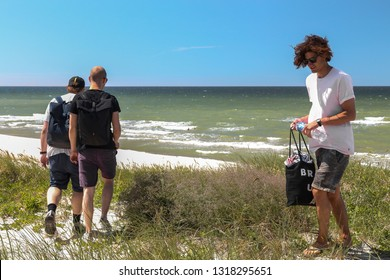 Nida, Lithuania - July 6, 2018: Group of young men on a Baltic sea beach in Nida - a popular summer resort in Lithuania, located on Curonian Spit.