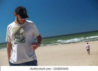 Nida, Lithuania - July 6, 2018: Two young men on a Baltic sea beach in Nida - a popular summer resort in Lithuania, located on Curonian Spit.