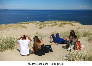 Nida, Lithuania - July 7, 2018: Groupd of young tourists on Parnidis (parnidzio) sand dune. One the the most beautiful and popular tourist points. Located in Nida, Curonian Spit. Unesco heritage site.