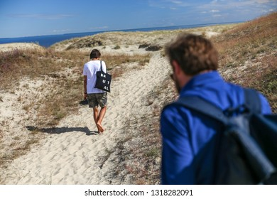 Nida, Lithuania - July 7, 2018: Young men are walking on Parnidis (parnidzio) sand dune. One the the most beautiful and popular tourist points. Located in Nida, in Curonian Spit. Unesco heritage site.