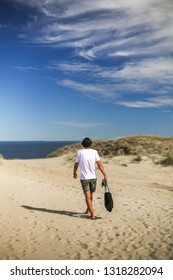 Nida, Lithuania - July 7, 2018: Young male is walking on Parnidis (parnidzio) sand dune. One the the most beautiful and popular tourist points. Located in Nida, in Curonian Spit. Unesco heritage site.
