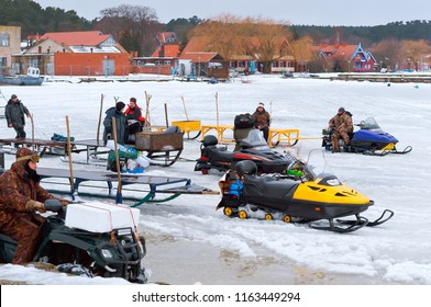 Nida, Lithuania, March 10, 2018, the fishermen on the ice ready to go in the electric sled farther from shore, snowmobiles for winter fishing