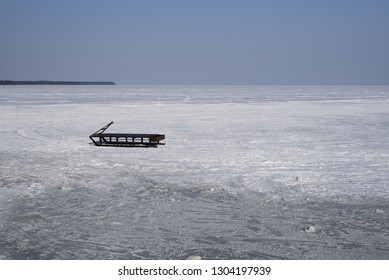 NIDA, LITHUANIA, March 2018. Ice fishing. Fishermen are transported to the fishing grounds by sleds. In the photograph, sledges can be seen in the background of the frozen Curonian Lagoon