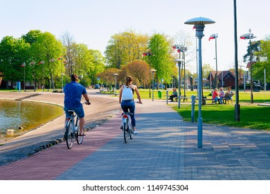 Nida, Lithuania - May 10, 2016: Couple riding a bicycle. Nida resort town near Klaipeda in Neringa, in the Curonian Spit and the Baltic Sea in Lithuania.