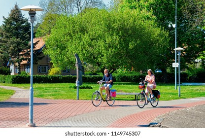 Nida, Lithuania - May 10, 2016: Senior people riding a bicycle. Nida resort town near Klaipeda in Neringa, in the Curonian Spit and the Baltic Sea in Lithuania.