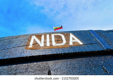 Nida, Lithuania - May 10, 2016: Fragment of wooden ship in Nida resort town near Klaipeda in Neringa on the Baltic Sea at the Curonian Spit, in Lithuania. Lithuanian flag