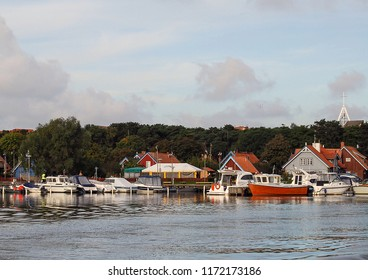 Nida, Lithuania - September 23 2007:    collection of small boats in the ahrbour of Nida with the curch steeple in the background