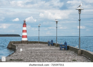 NIDA, LITHUANIA - September 7, 2017. Small red lighthouse on jetty breakwater and seagulls sitting on lamps
