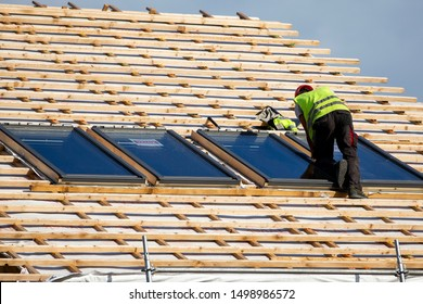 """Nida/Lithuania September 4, 2019 professional roofing craftsman shows new work: window skylight model """"velux"""" in roof with red tiles"""