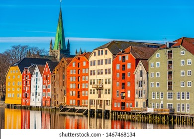 Nidaros cathedral and colorful timber houses surrounding river Nidelva in the Brygge district of Trondheim, Norway