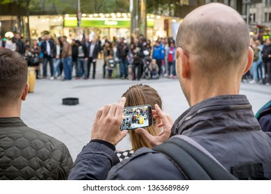 NIEDERSACHSEN, GERMANY SEPTEMBER 26, 2015: A GDPR data protection conceptual image of a man photographing and videoing street performers in public with a mobile smart phone.