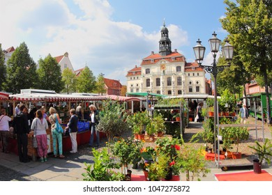 """Lüneburg, Niedersachsen/Germany – 08.21.2013: Market beside the Lüneburg Town Hall """"Marktplatz"""". Weekly market for fresh and quality products. you can see the front of the town hall."""
