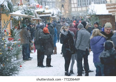 NIEDERSTETTEN, BADEN WUNTERBERG, GERMANY - December 10 2017: Traditional Christmas Market. People on the Street, Christmas Trees and Kiosks and Falling Snow.