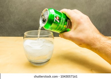 Niedomice, Poland - March 09, 2018: Pouring a carbonated drink 7up from a can into a glass with ice cubes.