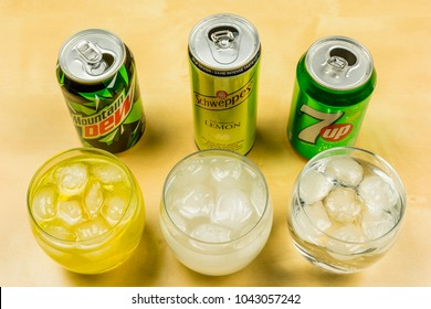 Niedomice, Poland - March 09, 2018: The cans of carbonated drink 7up, Schweppes and Mountain Dew were poured into glasses with ice cubes.