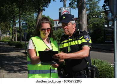 Nieuwerkerk aan den IJssel - Netherlands - May 15 2018 - bicycle exams for children on the streets by Safe Traffic Organization, police and municipality. Controll post and police officer discussing