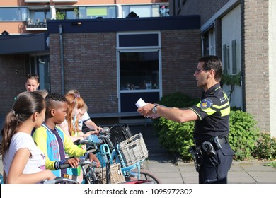 Nieuwerkerk aan den IJssel - Netherlands - May 15 2018 - bicycle exams for children on the streets by Safe Traffic Organization, police and municipality ,police officers gives instruction