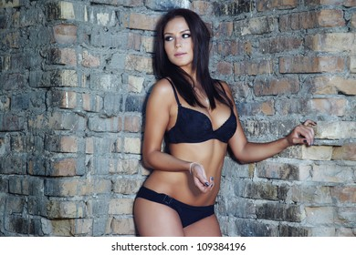 Nifty lady in underclothes with perfect figure standing in the brick corner