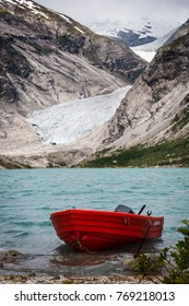 Nigardsbreen Glacier with lake and red boat in Norway