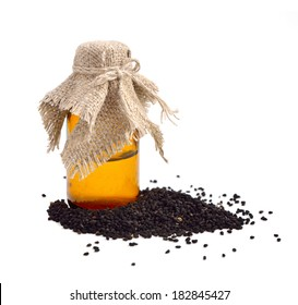 Nigella oil with seeds. Isolated on whitr background.