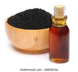 Nigella sativa or Black cumin with essential oil over white background