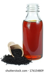 Nigella sativa (Black cumin) on wooden spoon and essential oil