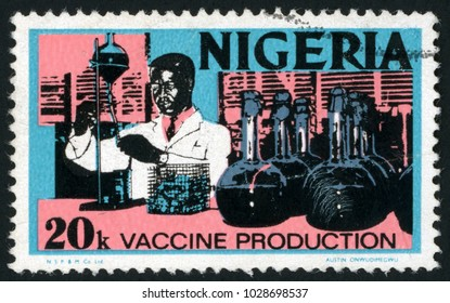 NIGERIA - CIRCA 1974: post stamp printed in Nigeria shows black man chemist doing tests with glass tubes; vaccine production; Scott 301 A78 20k pink blue; circa 1974