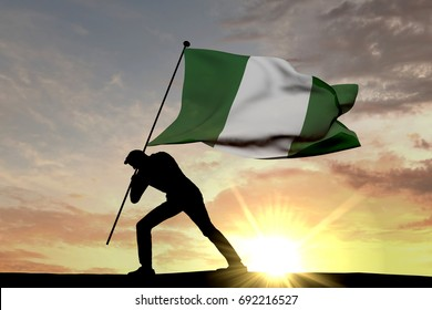 Nigeria flag being pushed into the ground by a male silhouette. 3D Rendering