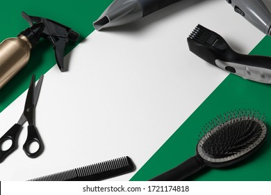 Nigeria flag with hair cutting tools. Combs, scissors and hairdressing tools in a beauty salon desktop on a national wooden background.