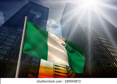Nigeria national flag against low angle view of skyscrapers at sunset