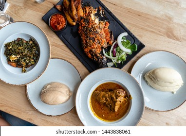 Nigerian food on table: Pounded yam, banga soup, fufu, semolina, semovita Eba Garri and Efo riro or Egusi soup, grilled fish and fried plantain. Lunch with friends