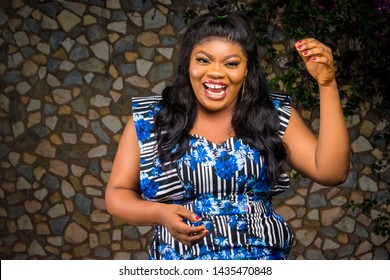 nigerian lady laughing really hard outdoor in late evening with a decorated wall and flowers in the background