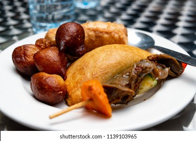 Nigerian meat pie, puff-puff, fish roll and stick meat gizzard pastries or Nigerian small chops in white saucer for Nigerian breakfast snack or food concept. Nigerian Food