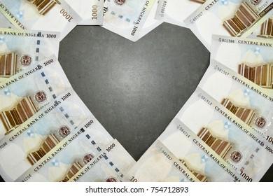 Nigerian Naira Money on dark background heart love shape