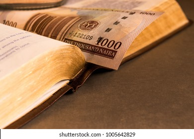 Nigerian Naira note money in open bible by candle light for church religious tithing