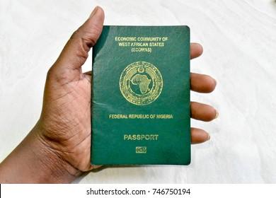 Nigerian Passport in African dark skin hand on white background isolated