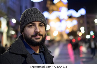 Nigh winter portrait of bearded man with hat in night scene looking at camera.