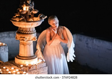 At night, the angel girl, blond-skinned standing in a white dress with wings near burning candles and suffering. architecture,  newspaper, advertising, model, ads, article, banner, poster,  photo