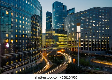 Night architecture - skyscrapers with glass facade. Modern buildings in Paris business district. Evening dynamic traffic on a street. Concept of economics, financial.  Copy space for text. Toned