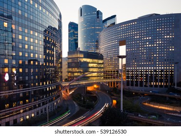 Photo of Night architecture. Skyscrapers with glass facade. Modern buildings in Paris business district. Evening dynamic traffic on a street. Business, economy and finances concept.  Copy space for text. Toned